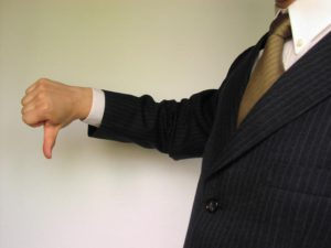 Man in suit pointing thumbs down